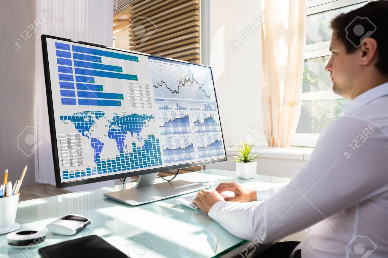 Young male stock market broker analyzing graph on computer at workplace - 106207214