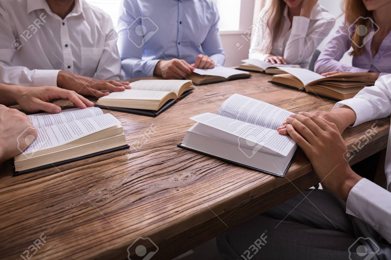 Group Of People Reading Bible On Wooden Desk - 107432753