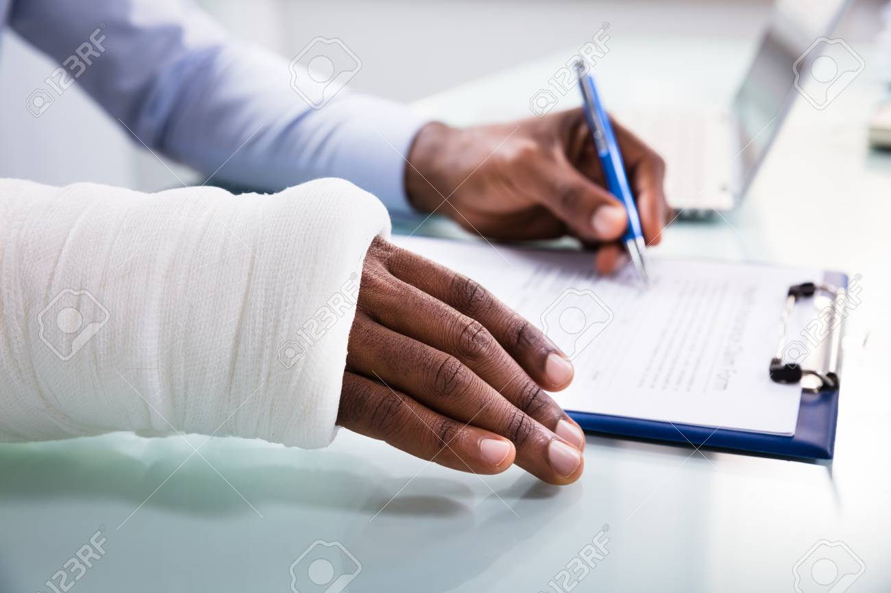 Overhead View Of Injured Man With Bandage Hand Filling Insurance Claim Form On Clipboard - 106566326