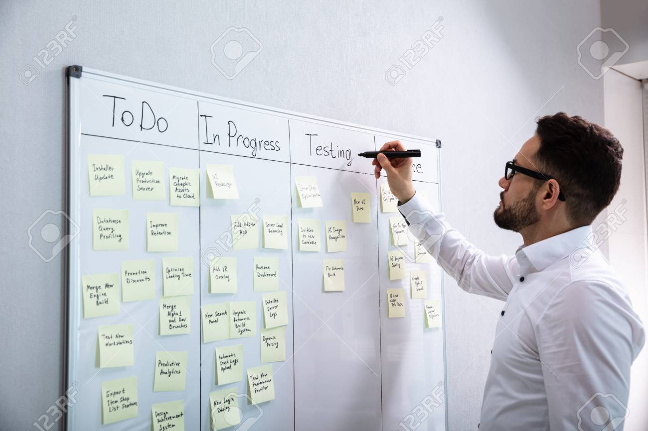Side View Of Businessman Writing On Sticky Notes Attached To White Board In Office - 120219025