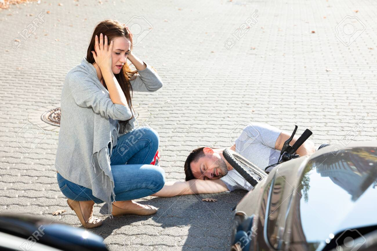 Young Woman Looking At Unconscious Male Cyclist Lying On Street