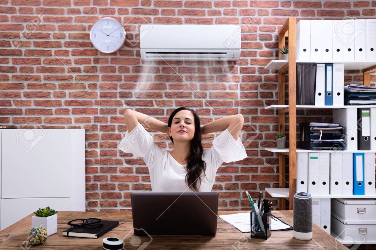 Relaxed Businesswoman Enjoying The Cooling Of Air Conditioner In The Office - 121140376
