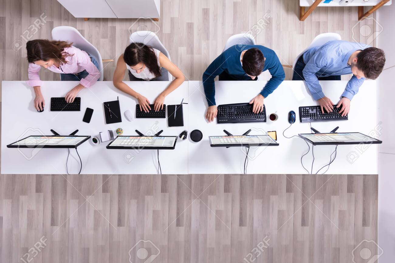 Young Businesspeople Analyzing Gantt Chart On Computer At Workplace - 121520014