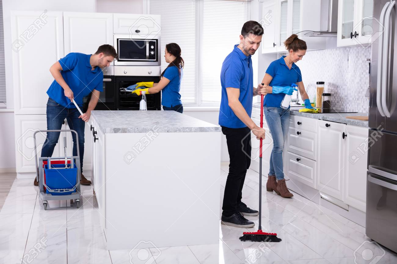 Group Of Young Janitors In Uniform Cleaning Kitchen At Home - 121987184