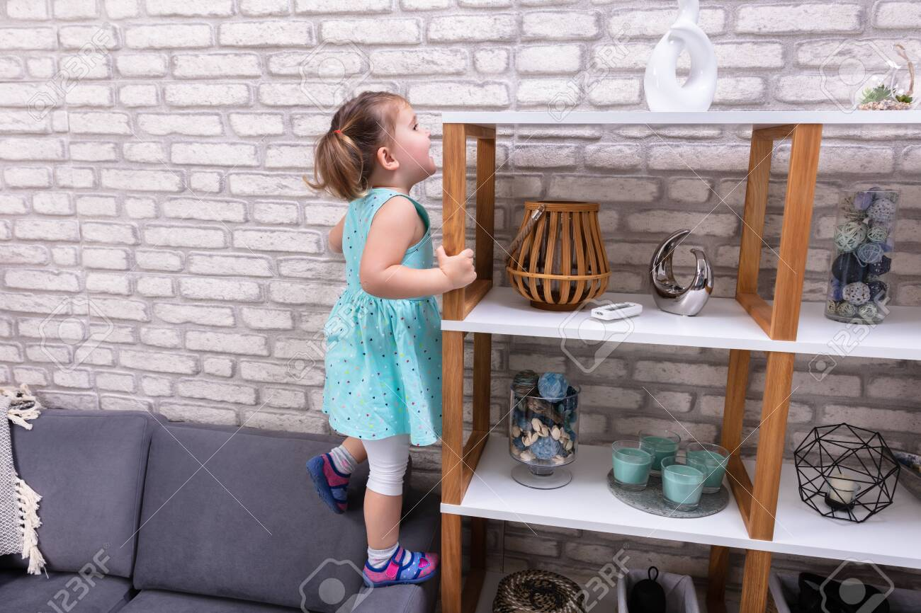 Cute Toddler Girl Standing On Sofa And Reaching For Toys On Shelf - 121987187