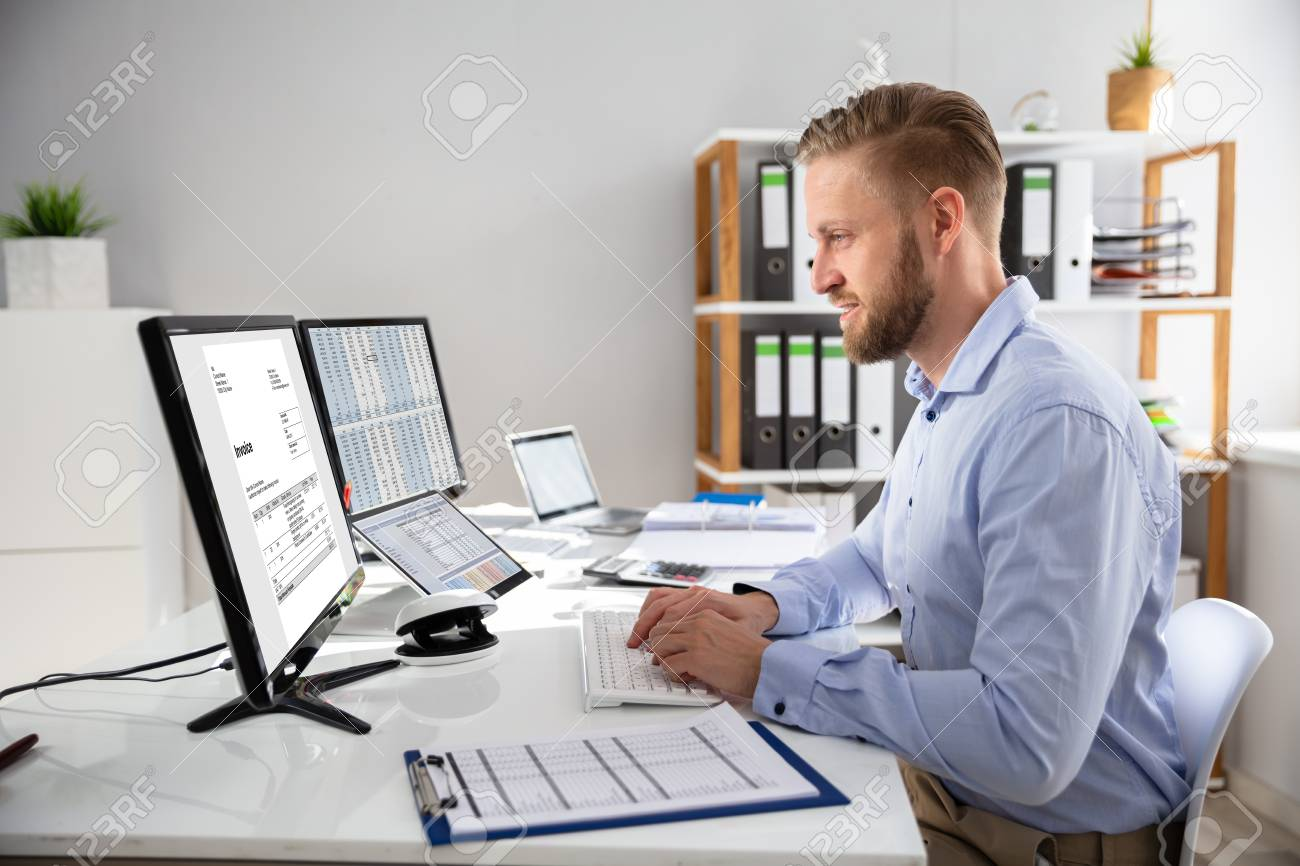 Businessperson Calculating E-Invoice Online On Computer At Office - 121987475