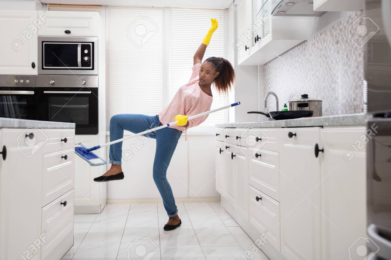 Close-up Of A Young African Woman Slipping While Mopping Floor In The Kitchen - 123418540