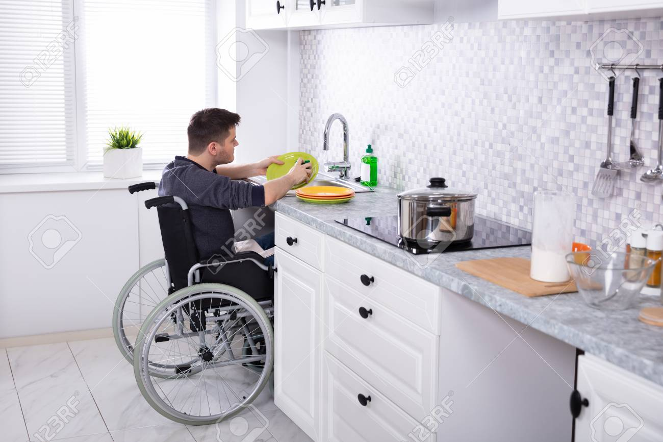 Handicapped Man Sitting On Wheelchair Washing And Cleaning Dishes In Kitchen - 123422341