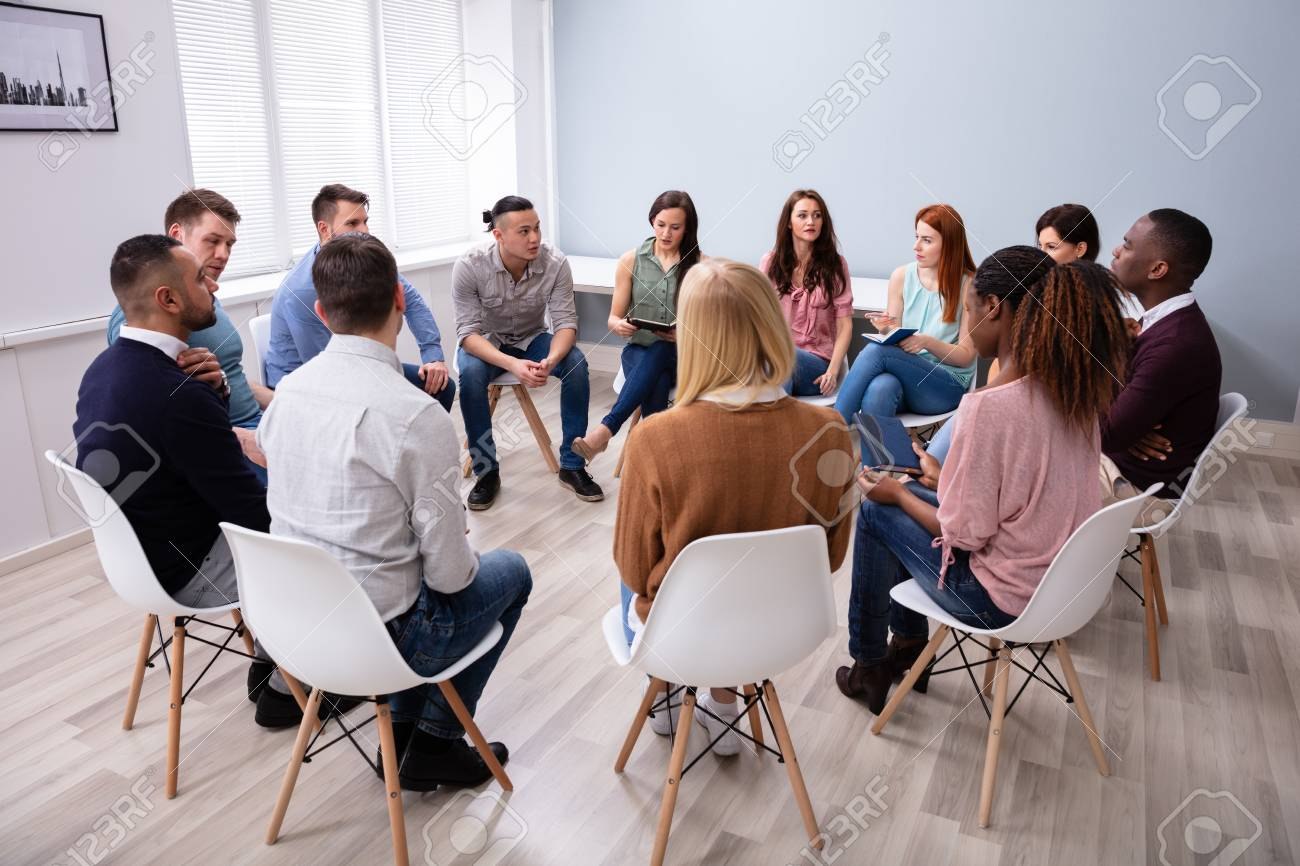 Young Multiracial Millennial Friends Sitting In Circle Having Group Discussion - 124600573