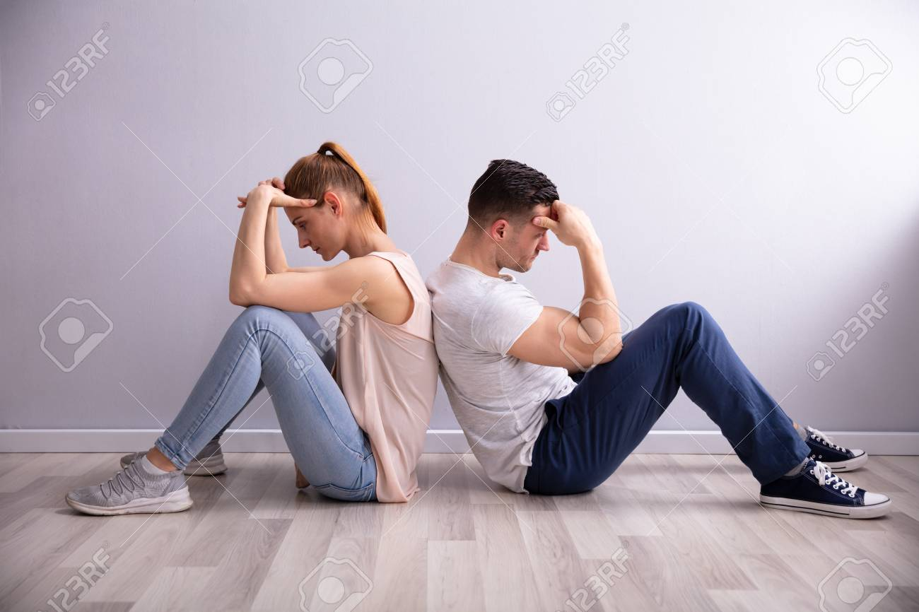 Sad Young Couple Sitting Back To Back On Floor At Home - 124601780