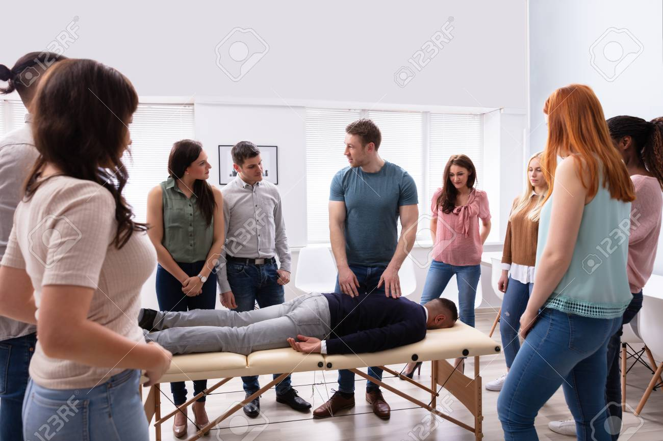 Male Instructor Teaching Massage Technique To Group Of Multi-ethnic People - 124677189