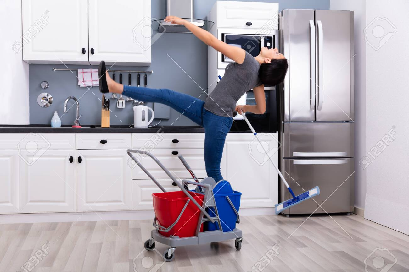 Close-up Of A Young Woman Slipping While Mopping Floor In The Kitchen - 128065469