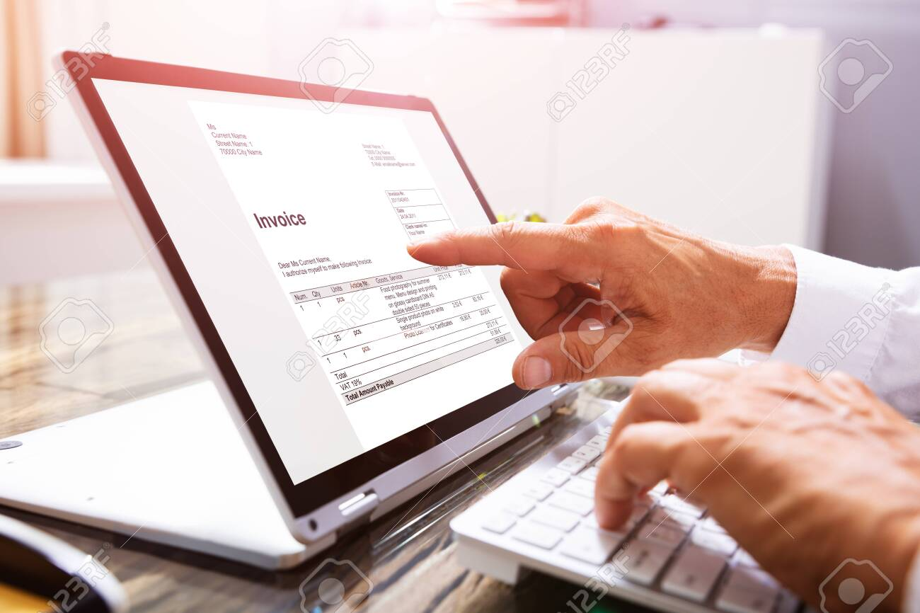 Close-up Of A Businessperson's Hand Analyzing Invoice On Laptop At Workplace - 128301325