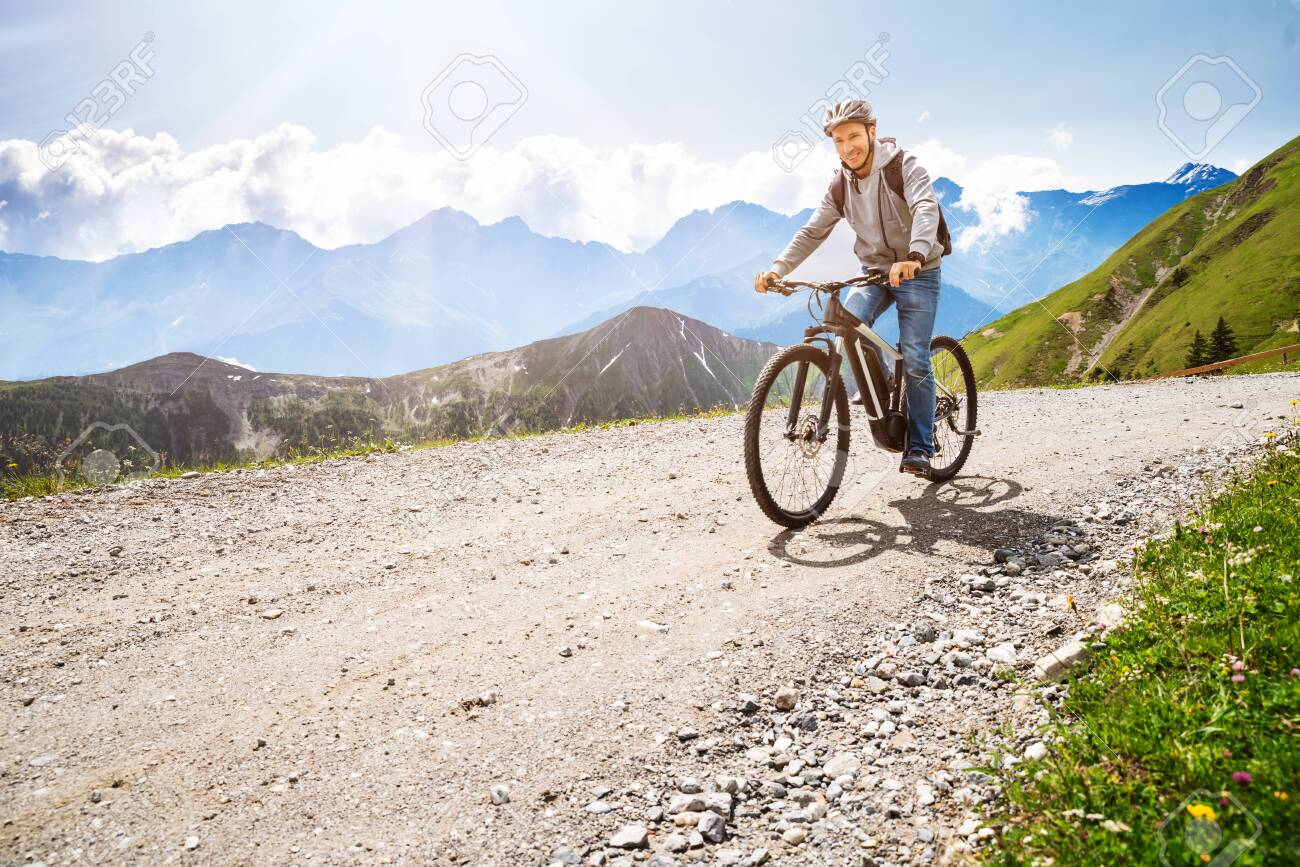 Man Riding Electric Mountain Bike In Alps - 128600027