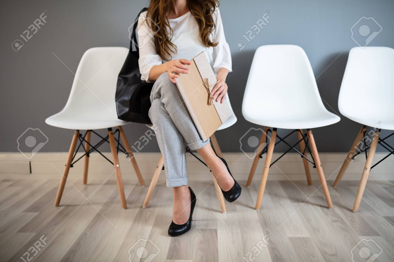 Young Businesswoman Holding Folder While Sitting On Chair Waiting For Job Interview - 128599363