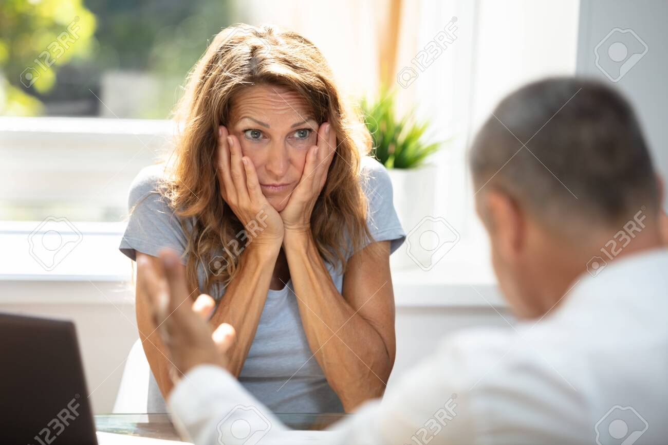 Unhappy Woman Looking At Her Colleague While Sitting In Office - 129097597