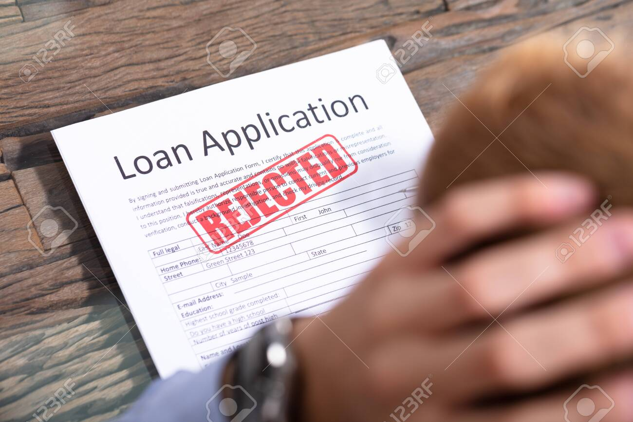 Stressed Person Looking At Rejected Loan Application - 129802598