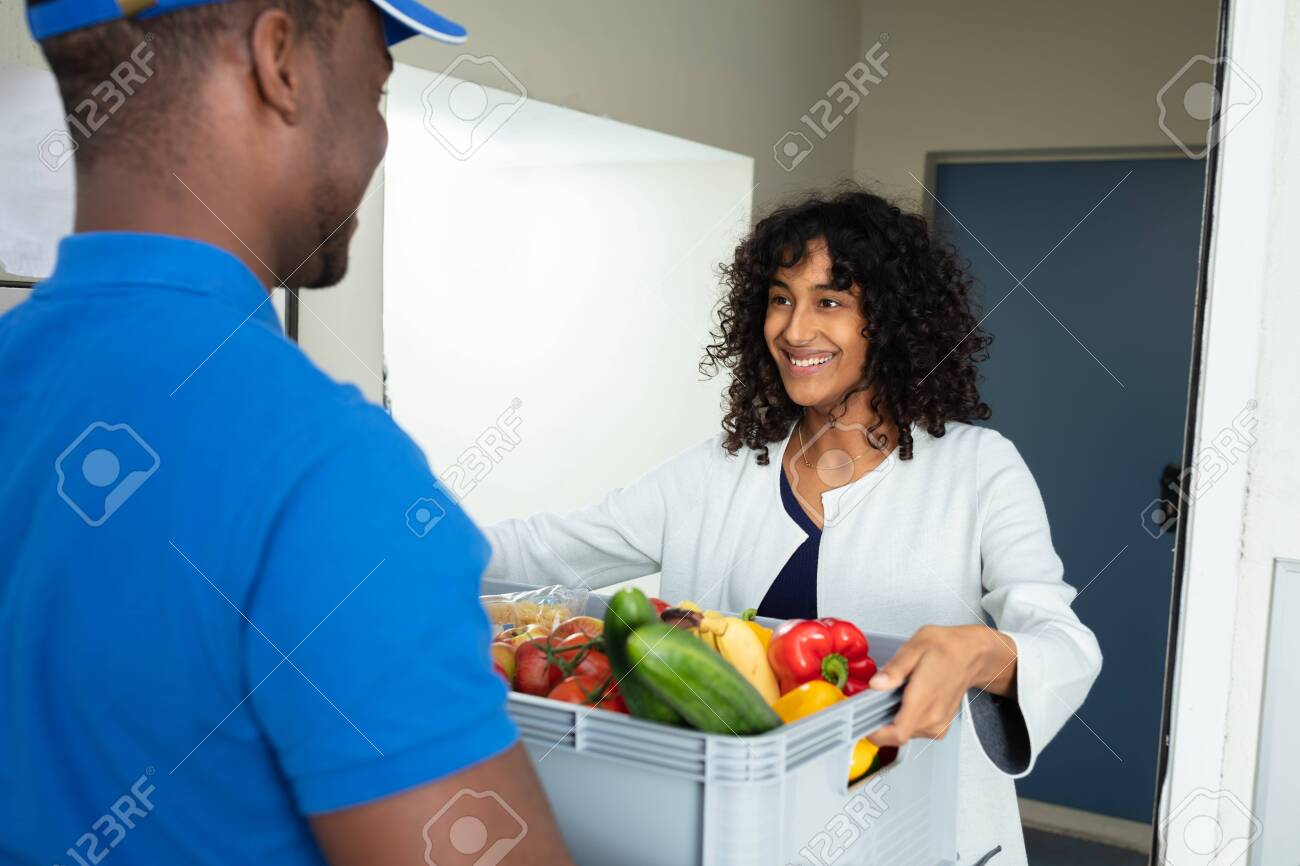 Smiling Woman Receiving Grocery Delivery At Home - 130637219