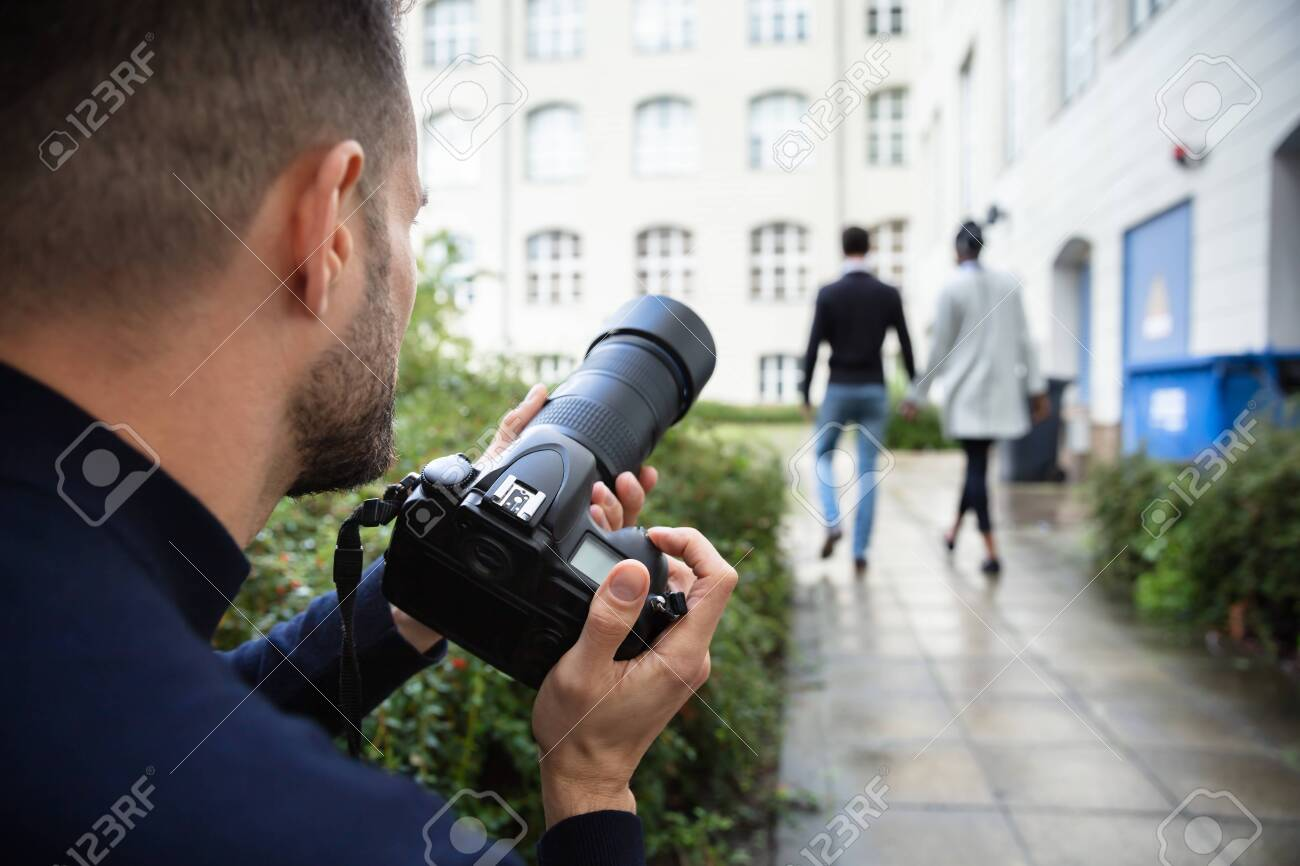 Young Man Paparazzi Photographer Capturing A Photo Suspiciously Of Couple Walking Together Using A Camera - 130976188