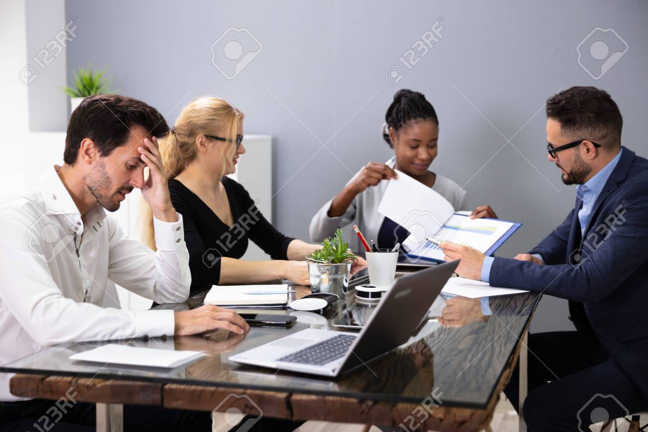 Bored Male Manger Sitting With His Colleagues Giving Presentation In Meeting At Office - 130976246