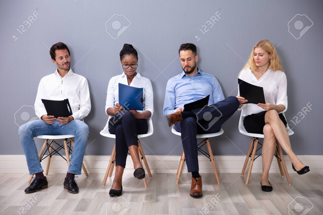 Multiethnic Businesspeople Sitting On Chairs In Row Waiting For Job Interview Against Gray Wall - 130976048