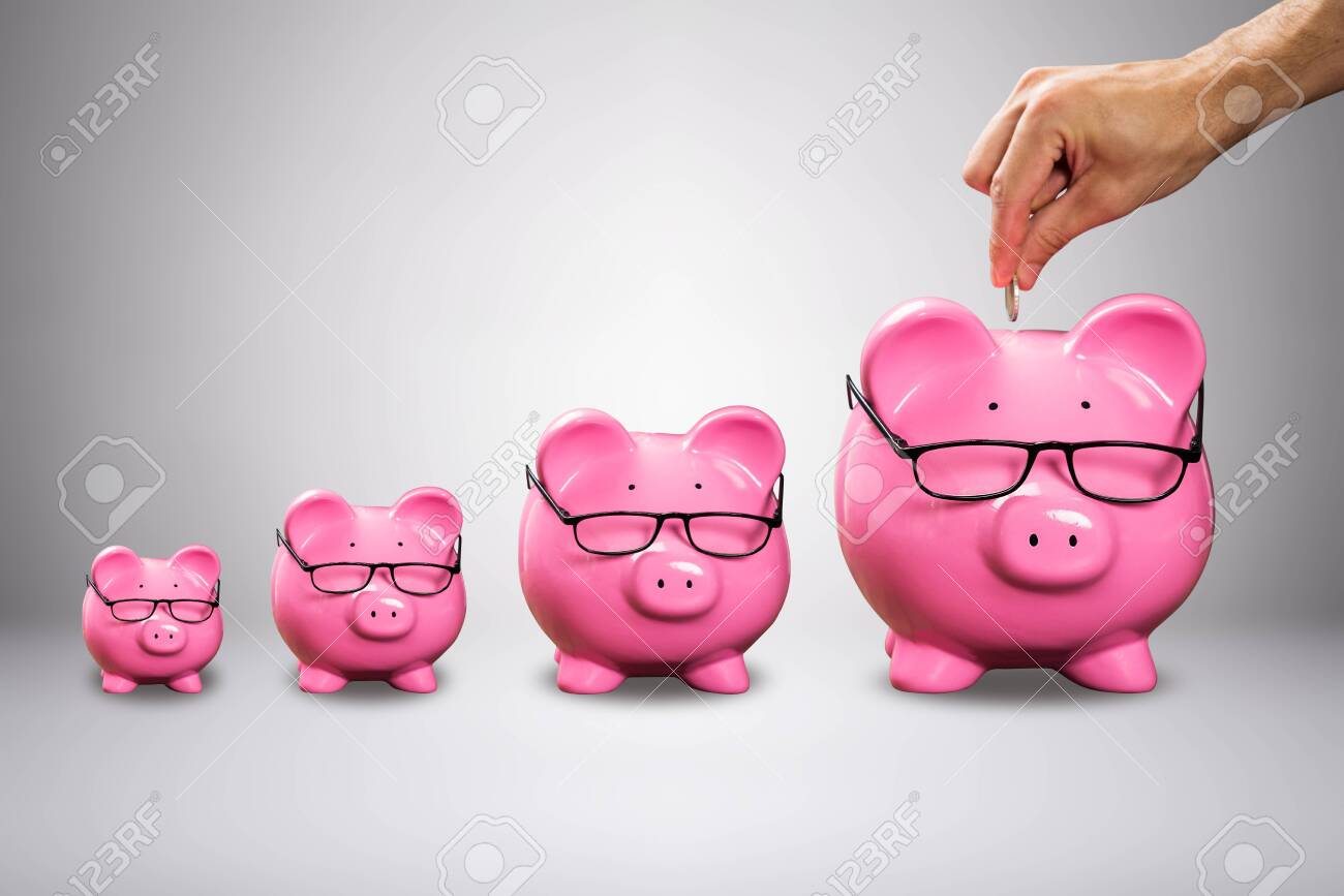 Man's Hand Inserting The Coin In Large Pink Piggybank With Eyeglasses Against Grey Background - 133291633