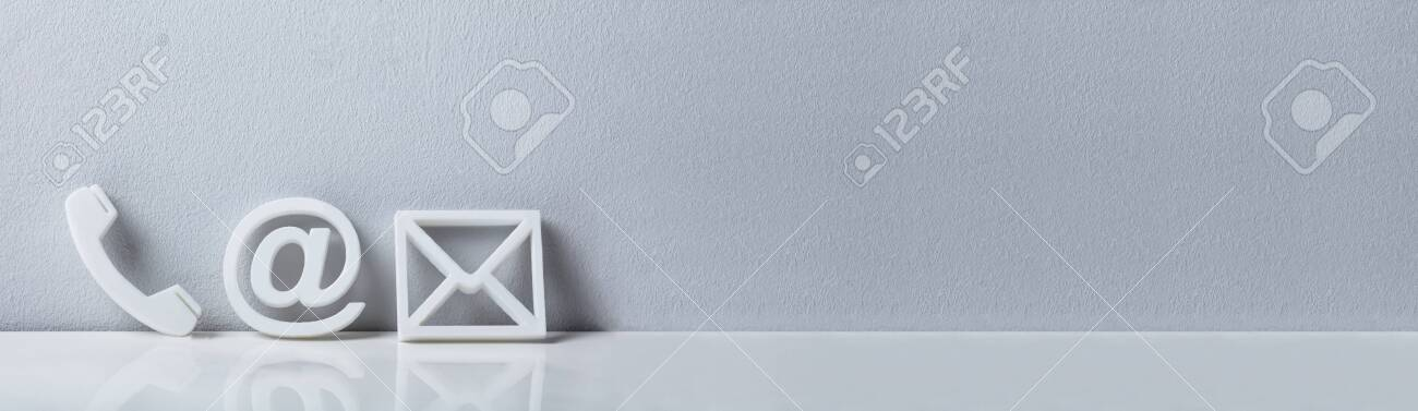 White Popular Contact Web Icons On Desk Over The Reflective Desk Against Gray Wall - 133291645