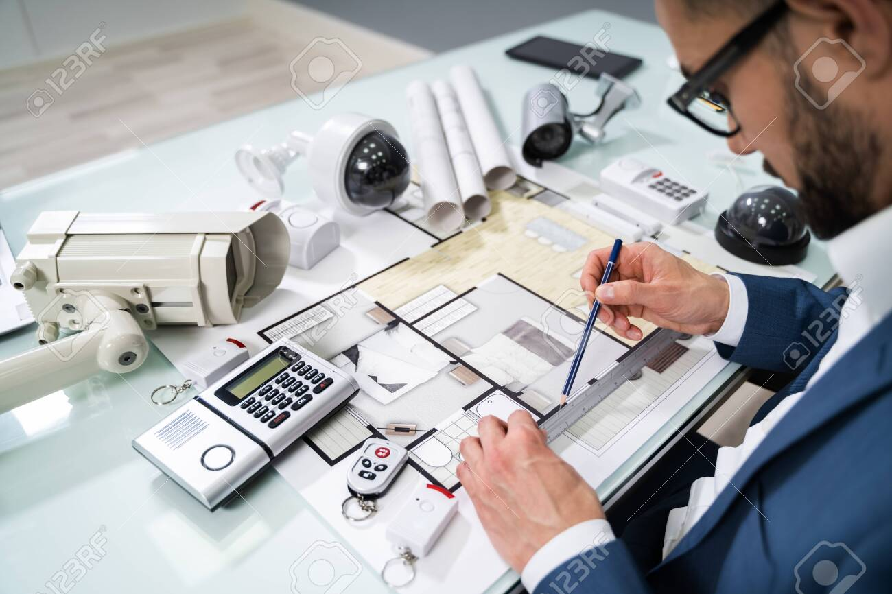 Architect Drawing Blueprint With Various Security Equipment On Desk - 142117677