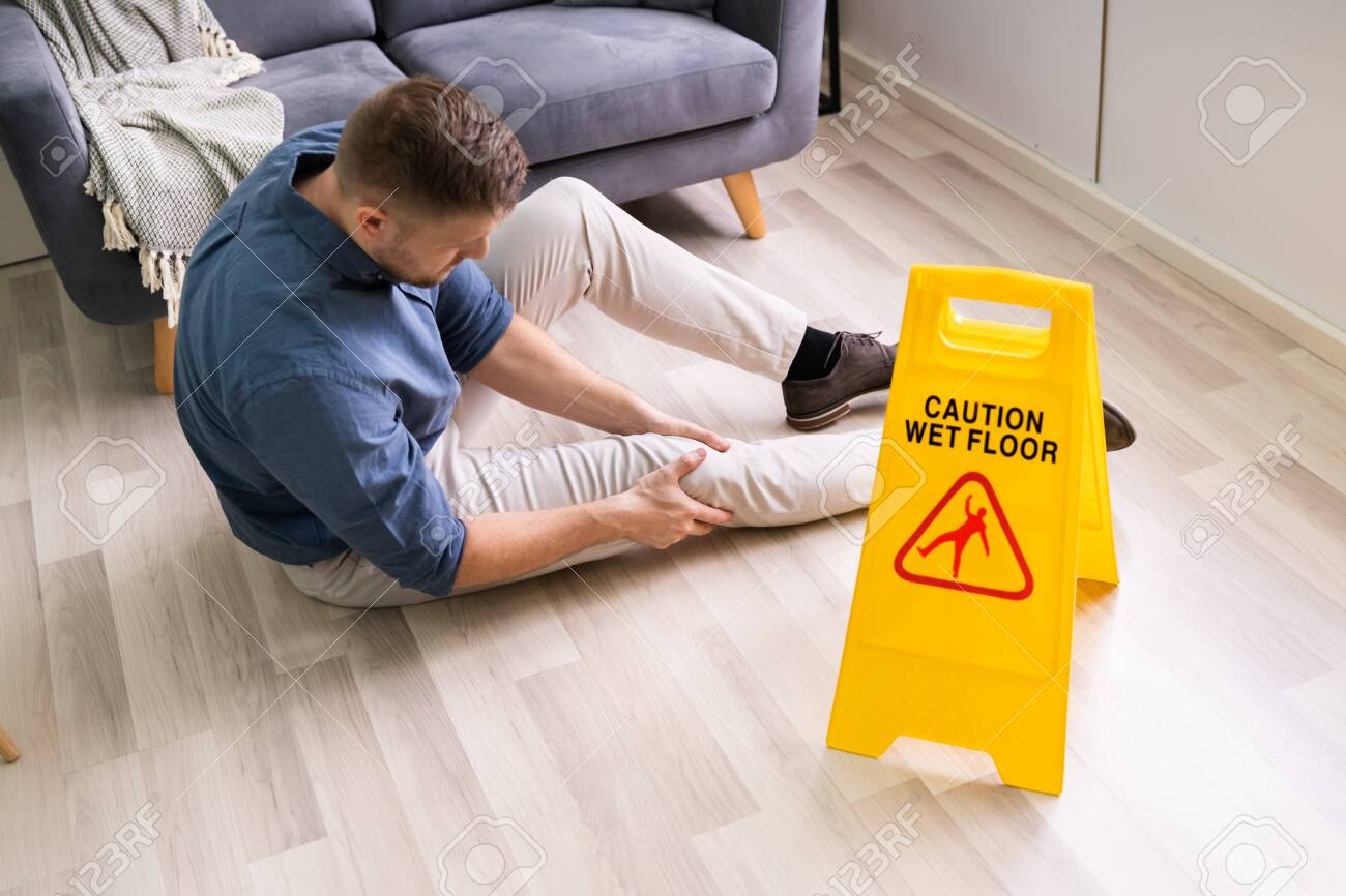 Man Falling On Wet Floor In Front Of Caution Sign At Home - 142822690