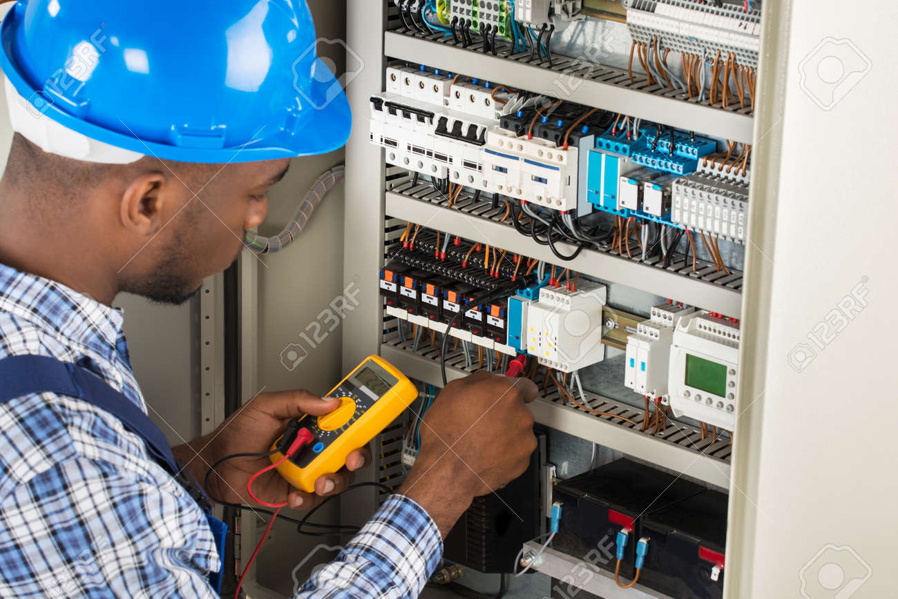 Close-up Of Male Electrician Checking Fuse Box With Multimeter - 166660857