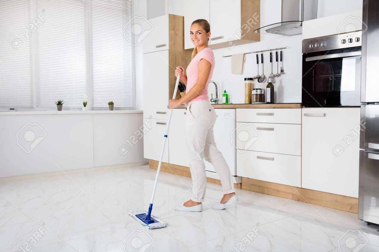 Smiling Cleaning Service Woman With Mop Cleaning Floor In The Kitchen At Home - 166659809