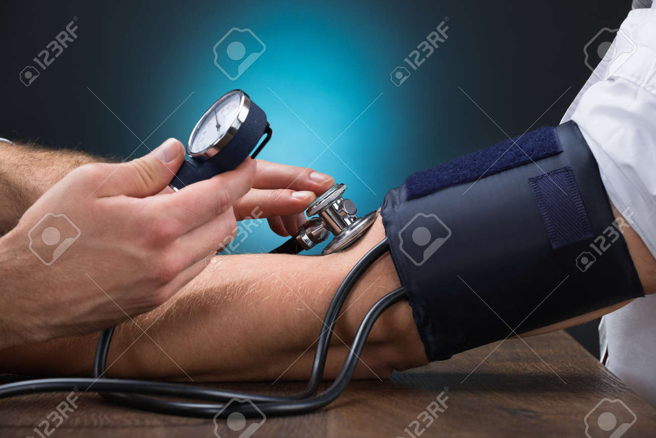 Cropped image of male doctor checking blood pressure of patient at table - 166674649