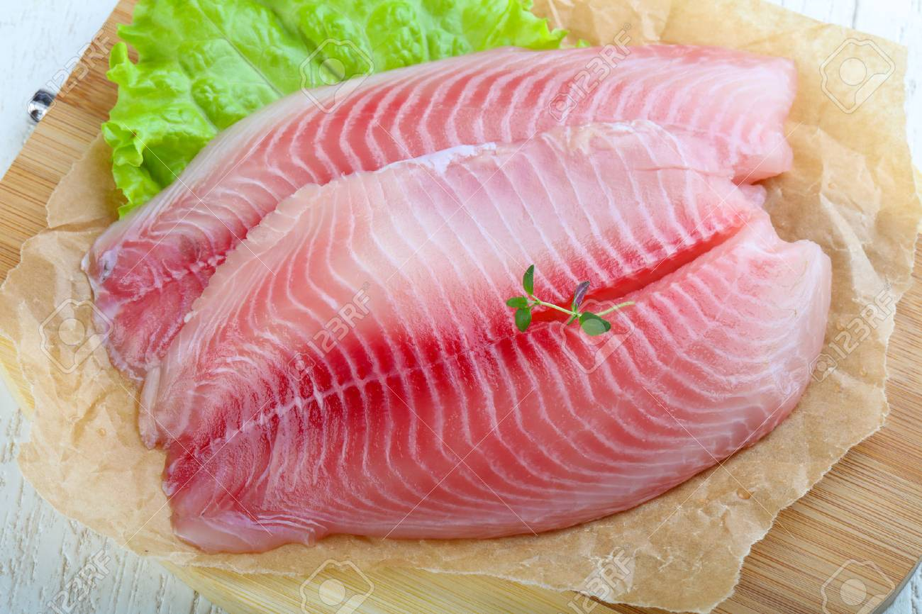 Raw Tilapia Fish Fillet With Thyme Ready For Cooking Stock Photo Picture And Royalty Free Image Image 56835887