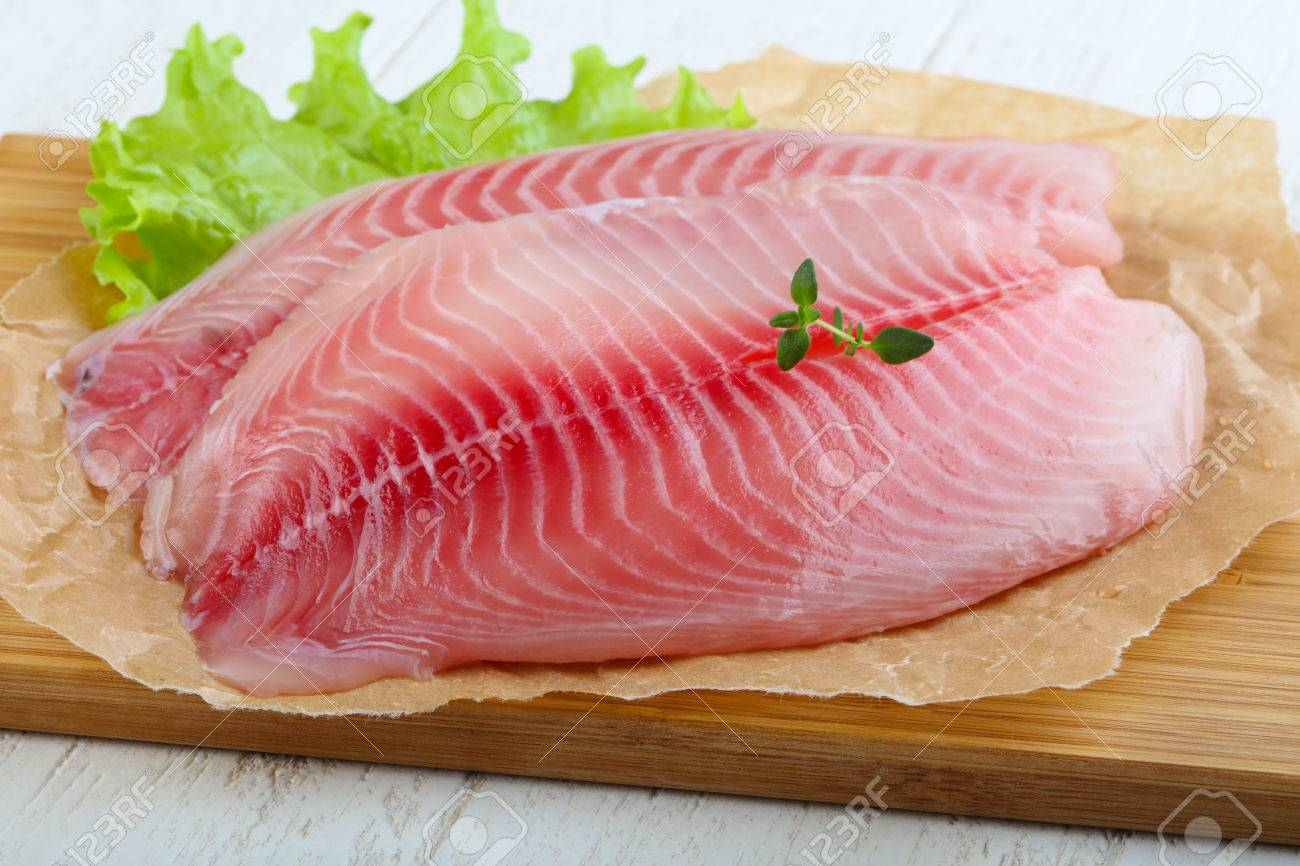 Raw Tilapia Fish Fillet With Thyme Ready For Cooking Stock Photo Picture And Royalty Free Image Image 61477430