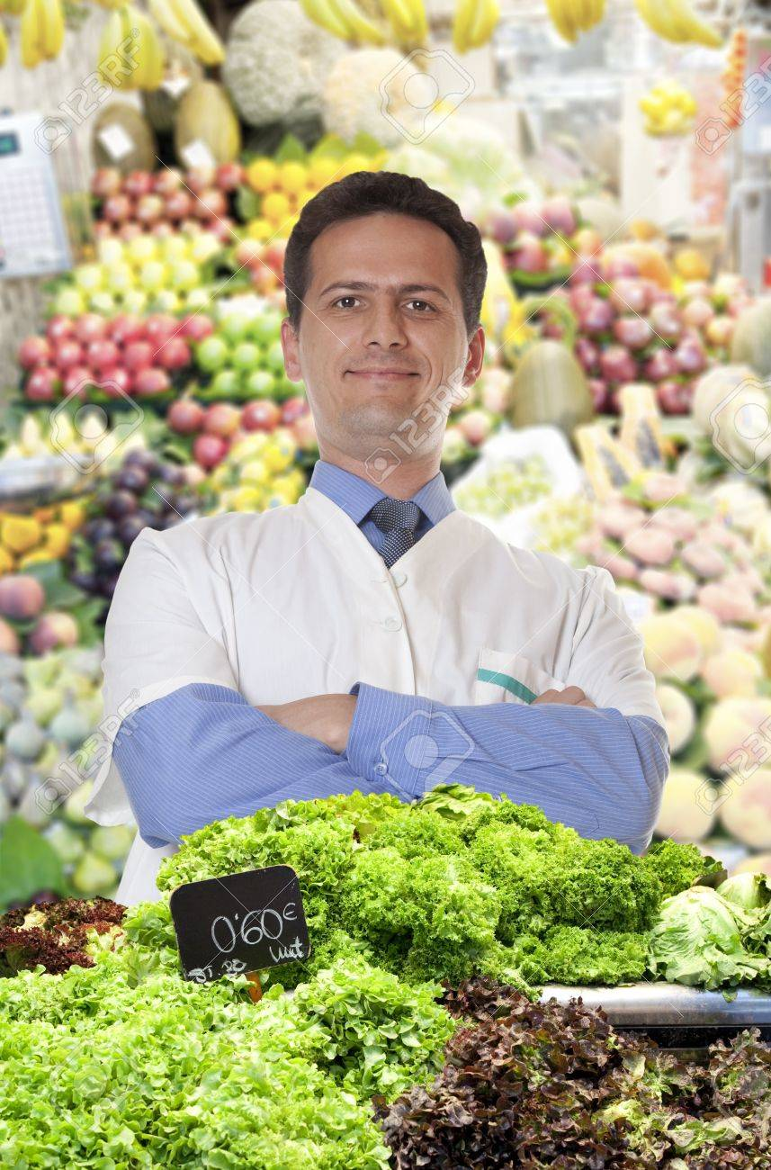 A young merchant of fruits and vegetables at the market sells lettuce Stock Photo - 15484358