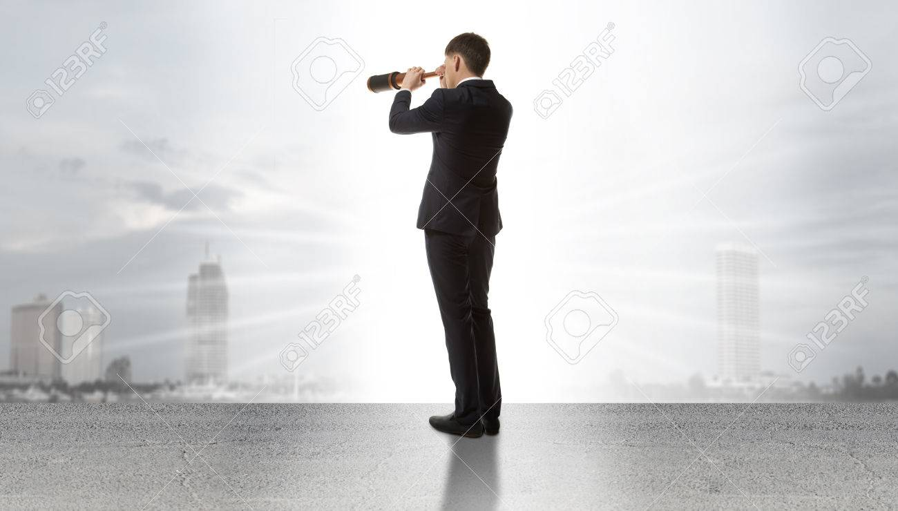 Businessman standing on a on road and looking through a telescope at city - 38886015