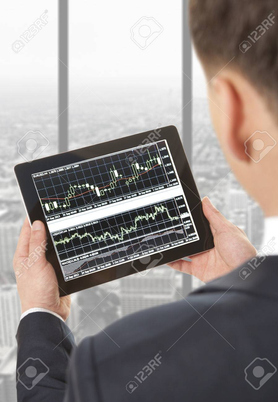 Businessman checking the stock market on digital tablet in office - 39504400