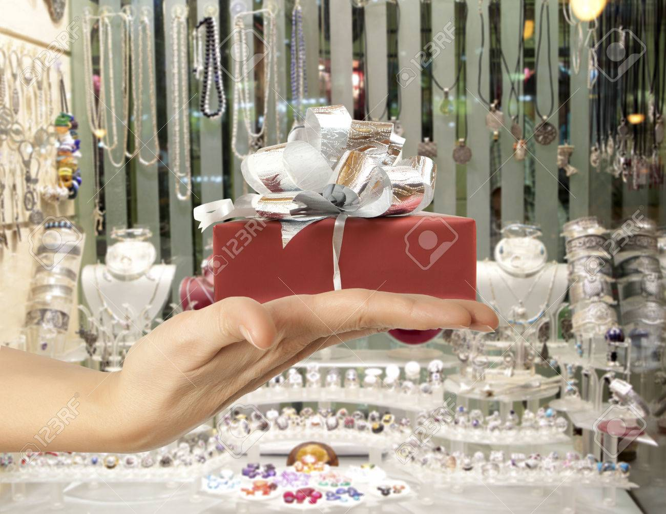 Female hand holding a gift in the background jewelry shop window - 50364504