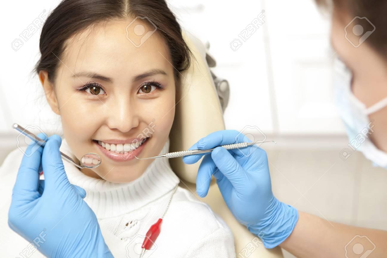 Smiling patient looking at camera while dentist examining it. Dental photo series - 51997361