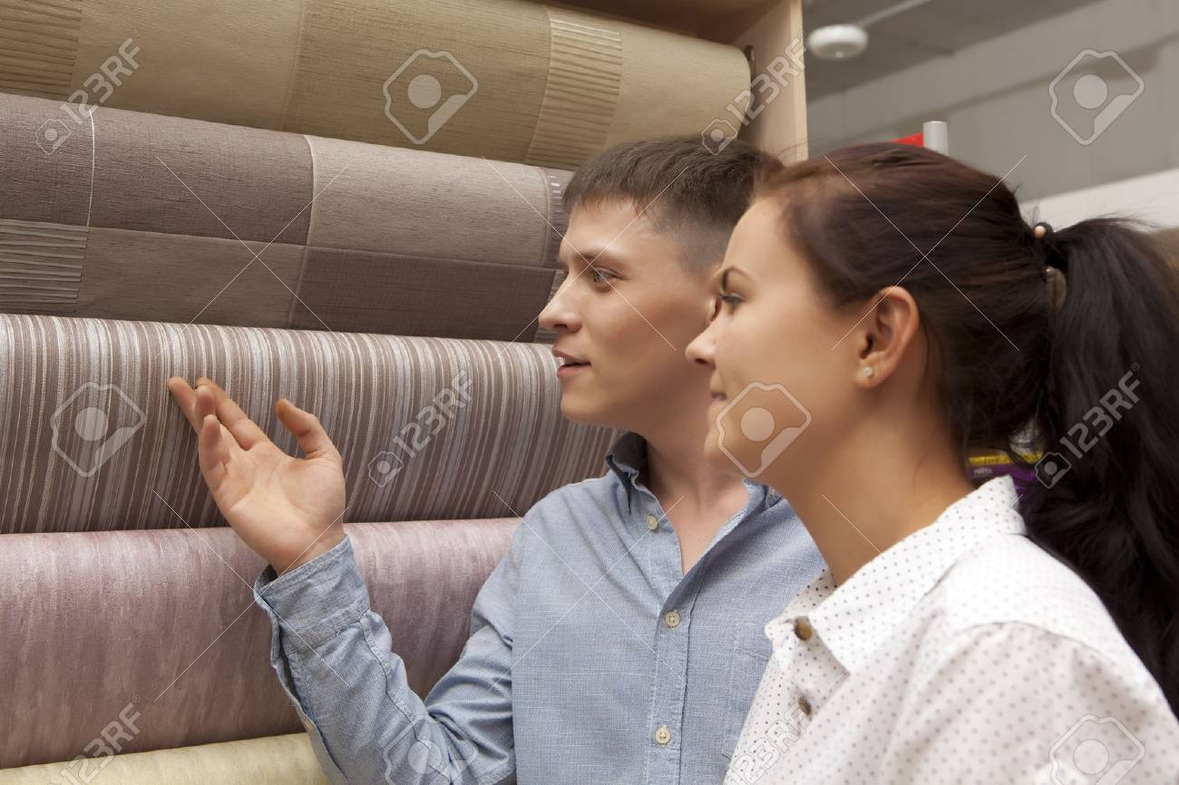 Happy family couple having fun in store choosing for buying wallpaper looking at design image - 59608265
