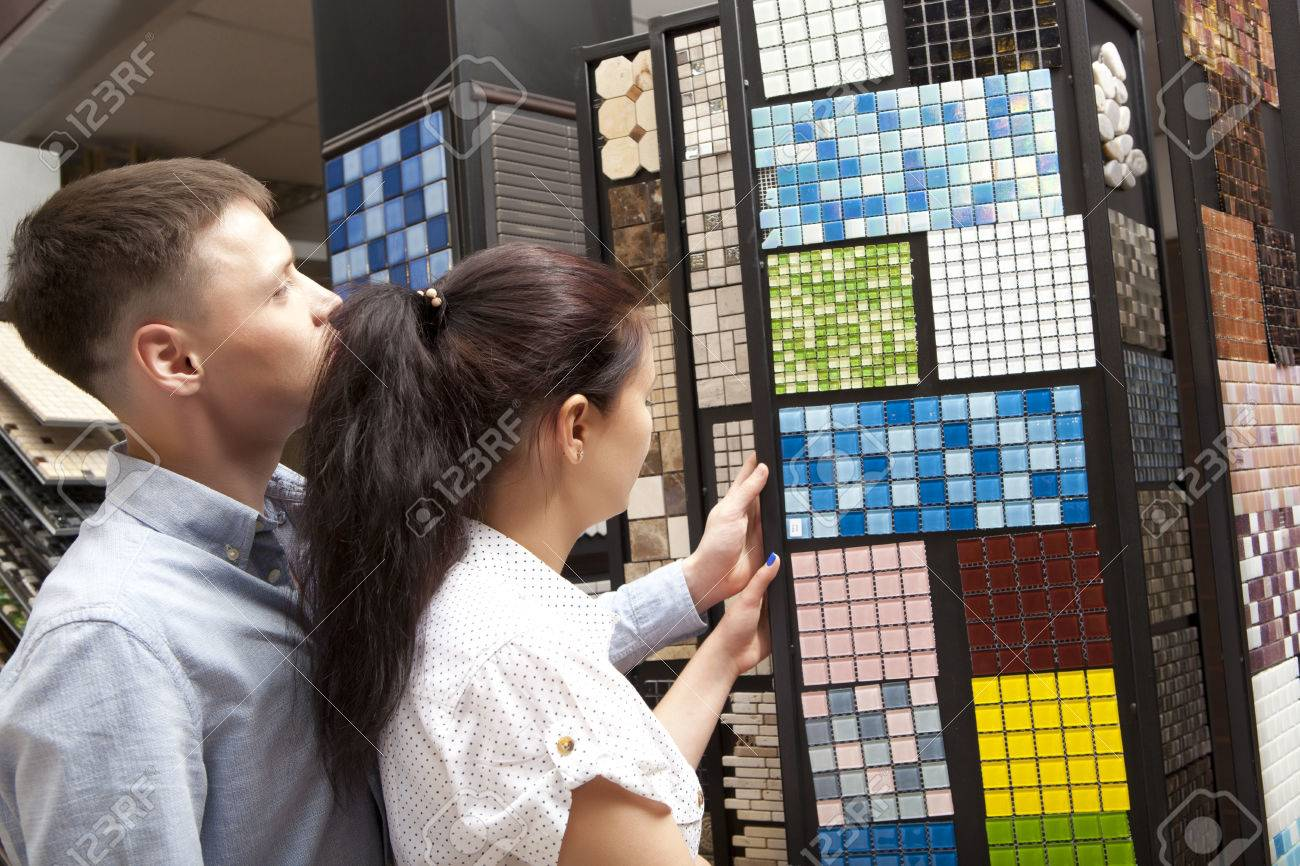 Couple pointing at ceramic mosaic tile for bathroom wall in store, in home improvement warehouse exterior - 64184513