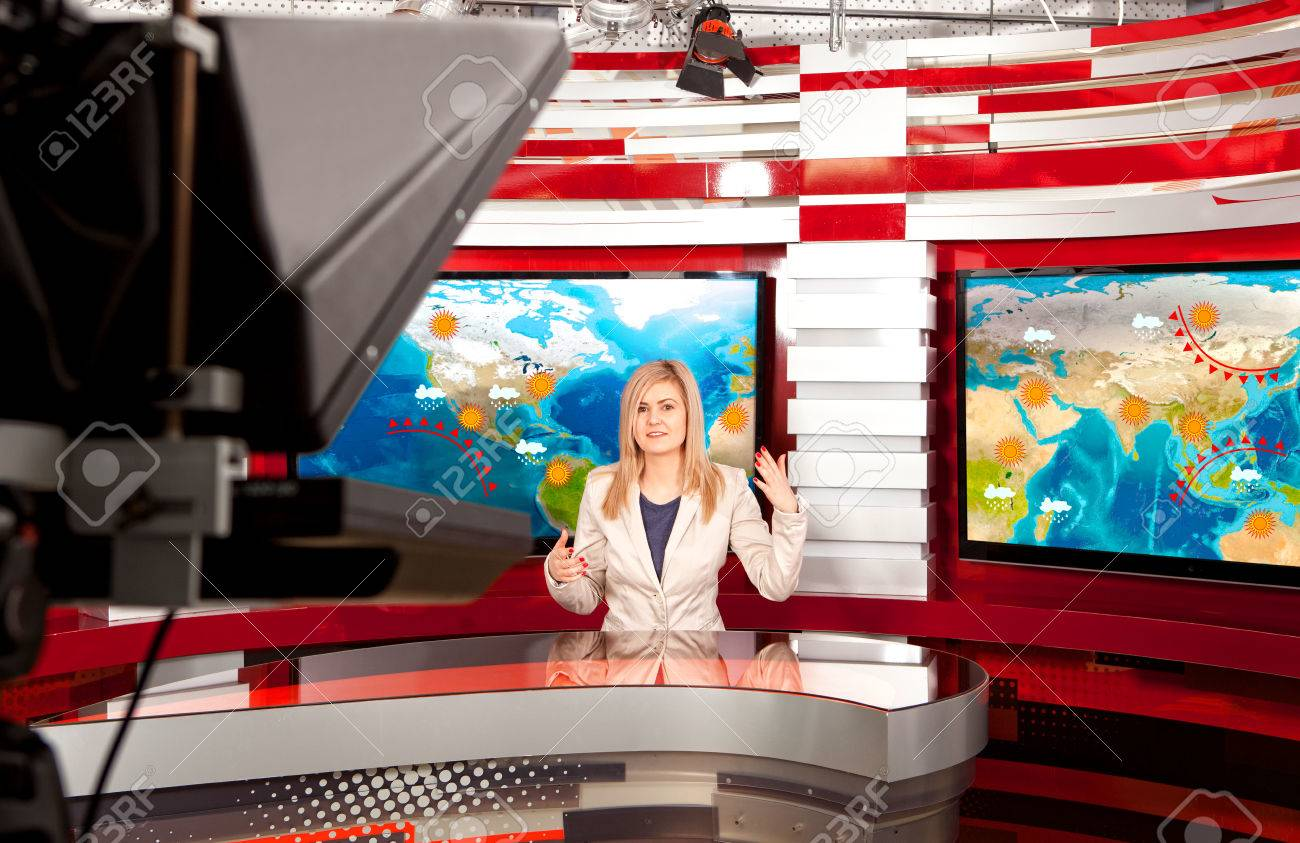 Weather forecast. A television anchorwoman at studio during live broadcasting - 78457780