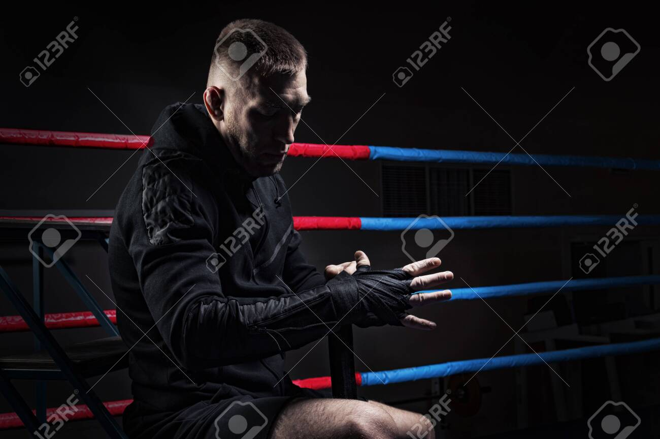 Mixed martial artist wraps bandages around his fist. Concept of mma, ufc, thai boxing, classic boxing. Mixed media - 143817850