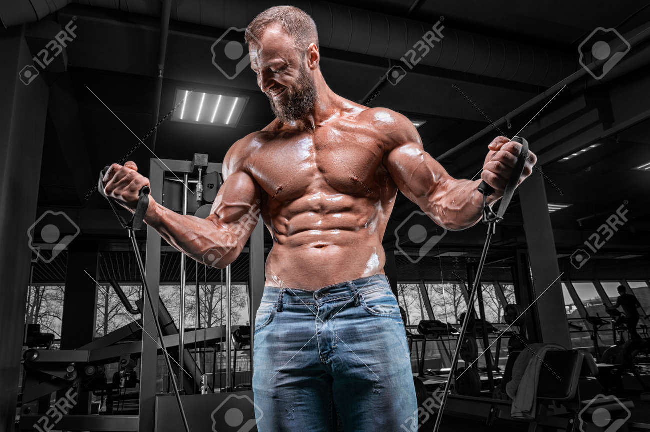 Professional athlete trains with elastic bands in the gym. Bodybuilding and fitness concept. Mixed media - 167974035
