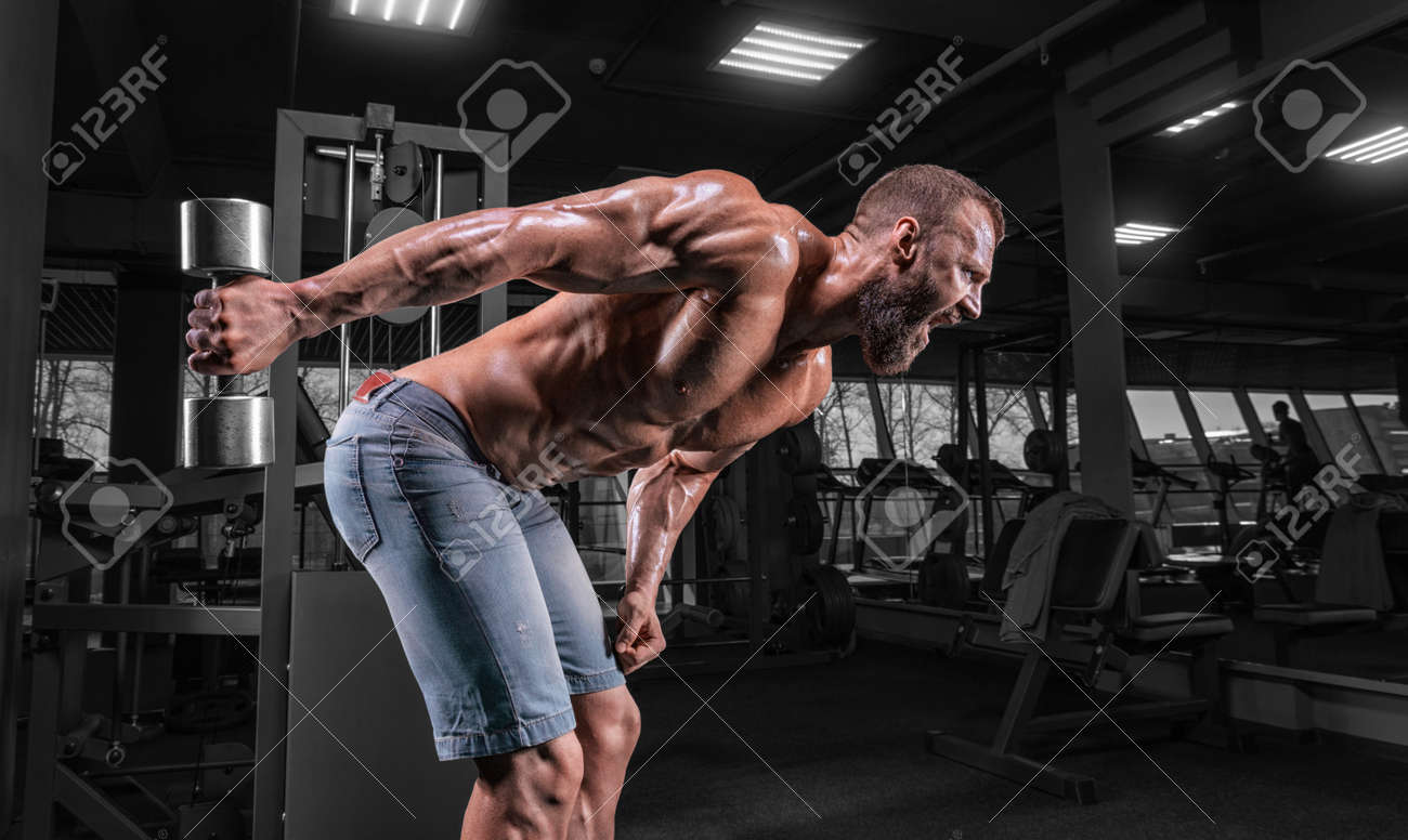 Professional athlete trains with a dumbbell in the gym. Triceps pumping. Bodybuilding and fitness concept. Mixed media - 167974051