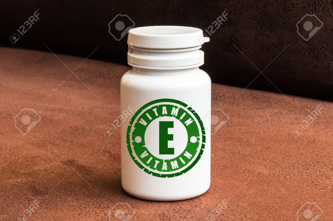 Bottle of pills with vitamin E on brown background Stock Photo - 73507353