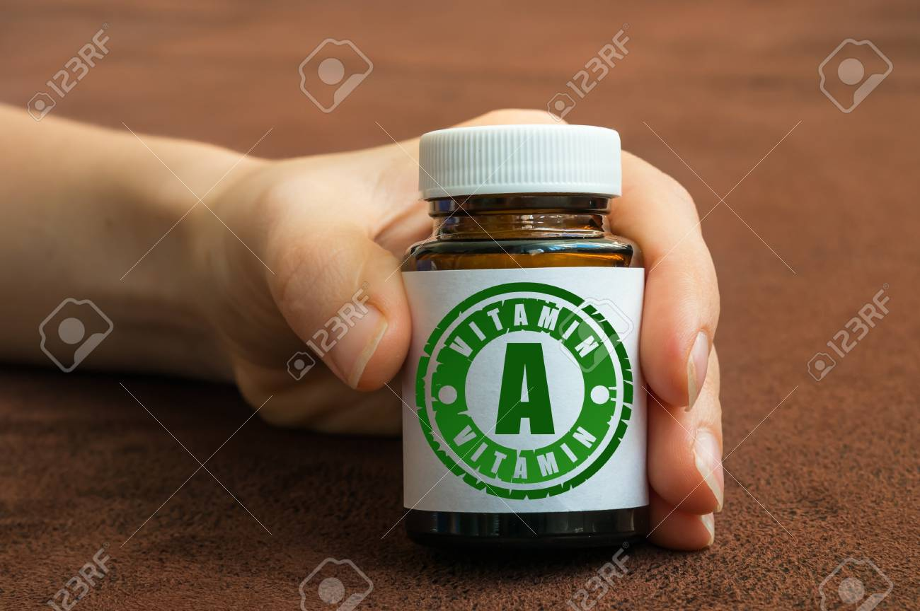 Human hand holding a bottle of pills with vitamin A on brown background Stock Photo - 73493802