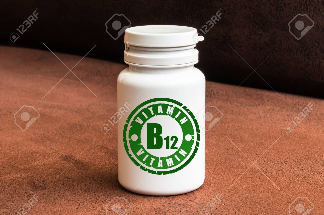 Bottle of pills with vitamin B12 on brown background Stock Photo - 73494195