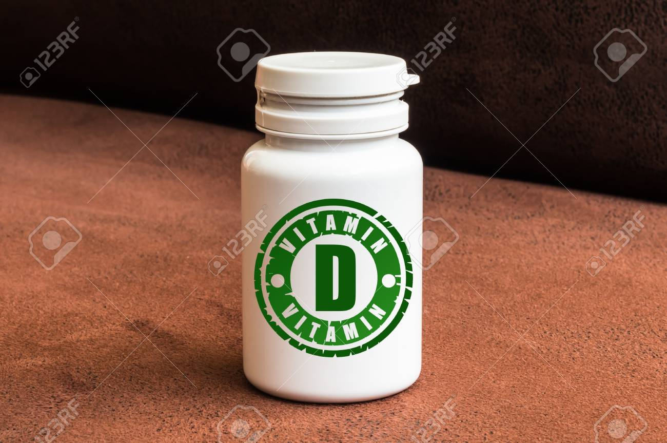 Bottle of pills with vitamin D on brown background Stock Photo - 73508061