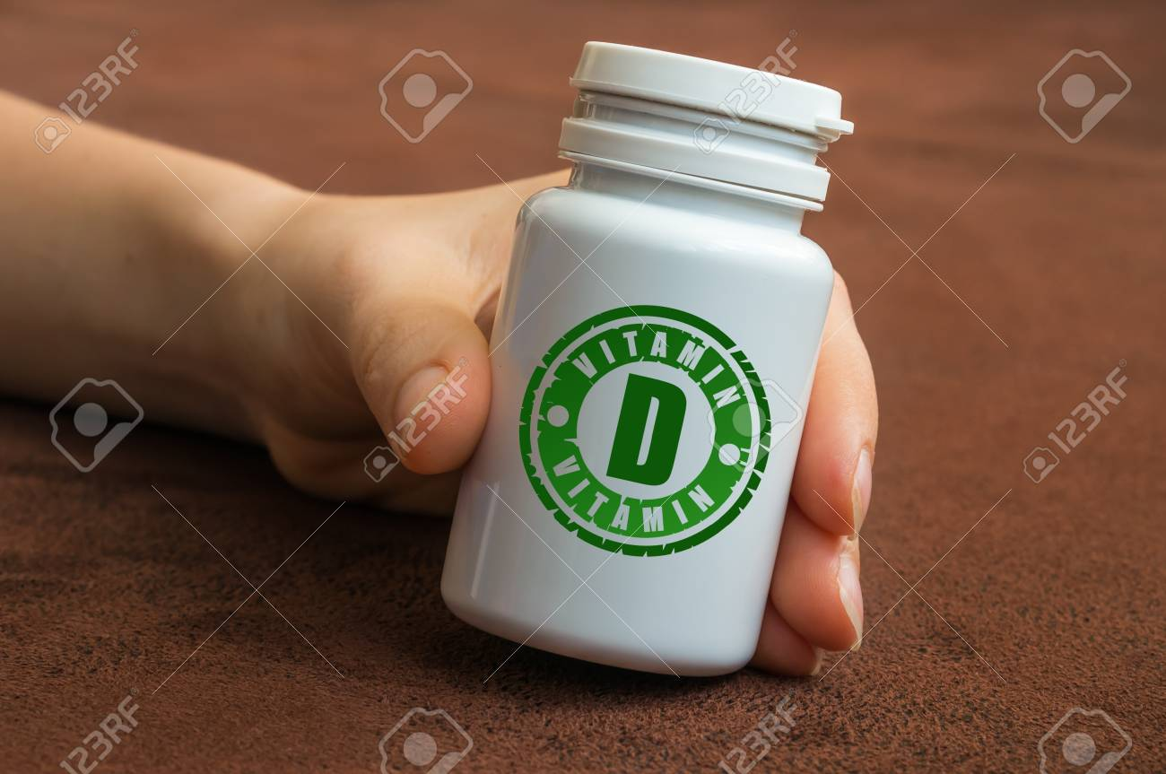 Human hand holding a bottle of pills with vitamin D on brown background Stock Photo - 73525389